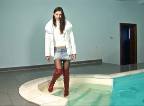 Wearing long red leather boots, black pantyhose, denim mini skirt, white sweater and white winter jacket, Mihaela is ready for playing in the pool. First, she sits by the steps and dips her red boots and denim skirt into the pool. She then ventures furthe
