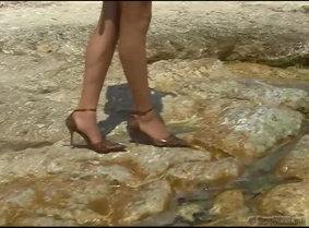 Tania in white outfit and brown heels enjoy the water.