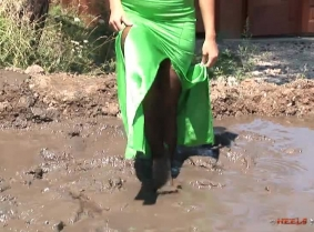 Maya is wearing this time a superb green evening gown, brown pantyhose and black patent heels. And of course she play in the mud till she get all covered with it.