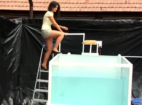 Eva is ready for a new dunking session. She is wearing short pants, pantyhose a yellow blouse which goes completely seethru when wet and of course heels.
