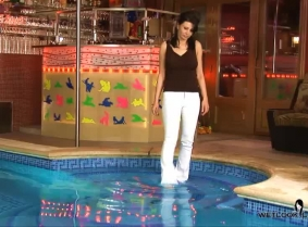 Dana is playing around in the pool wearing white pants, sandals and a sexy top.