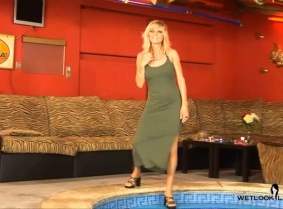Alexa is just relaxing herself in the pool, wearing a simple olive green mini-dress and a matching pair of heels.