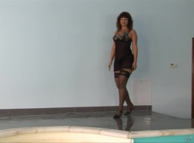 Kris is having a sexy swim into the pool. She is wearing a black negligee, stockings and heels.