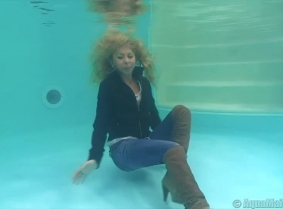 Julia swims and poses underwater, fully dressed.