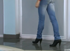 Adria is wearing a pair of jeans and a blouse with a denim vest and a pair of high heeled ankle boots.