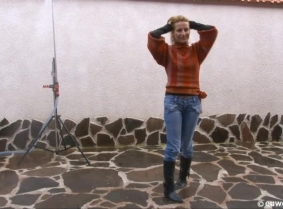 Lili is taking an outdoor shower, wearing a pair of jeans and a sweater with a black blouse underneath. The boots stay on during the whole clip and Liliane wears no bra under the blouse.