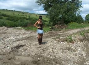 Eva is messing her expensive boots and sheer pantyhose into the mud.