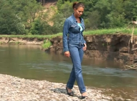 Maya is wearing a pair of Levi's along with a denim jacket and a pair of open toe heels. And she is playing and posing into a creek for our viewing pleasure.