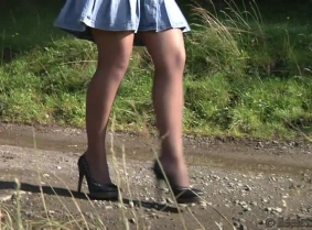 Rita is having a messy session next to a country road, covering her pantyhose and heels with thick mud.