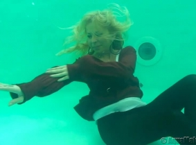 Julia is posing in our pool wearing a brown cardigan, opaque pantyhose heels and a white blouse.