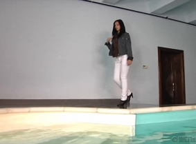 Irma is playing in the pool and posing for the cameras wearing a pair of tight with jeans with black pantyhose under and a denim jacket with a shirt under.