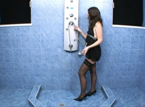 Adeline plays in the shower wearing a black negligee, stockings and heels.