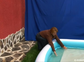 Lili is playing on the kiddy pool wearing a denim skirt, low heeled, cowboy boots and a brown cardigan over a black thin blouse.