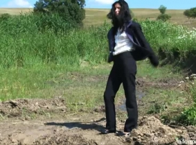 Christine is trashing a fine business suit into the mud. Watch her covering her clothes and heels completely with thick mud. Wash off session included.
