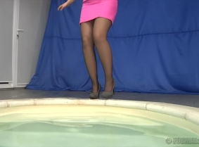 Emoke is wearing a little pink dress, black sheer stocking and grey pumps, and she is playing and swimming in the pool.