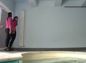 Alehandra and Oana are playing together in the pool. Both are wearing pink blouses which are thin enough to look great when wet, black leggings and high heels with nylon socks.