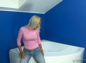 Judith is enjoying herself into a bath filled with warm water. She is wearing a pair of boots and blue jeans and a pink blouse with a bra underneath in the beginning. Then as the time passes, she removes the blouse and then her boots and jeans and after s