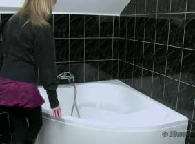 Noemi takes a shower wearing black leggings and boots and a velvet jacket on top of a thin black blouse. Her black clothes got a sexy shining when Noemi plays with the shower on them.