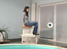 Kata is dunked in the pool, wearing one of her casual outfits. She wears a thin, grey blouse without bra underneath, a pair of jeans, casual shoes and nylon socks.  During the video Kata removed the heels.