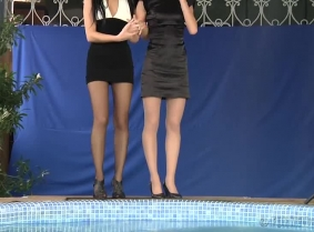 Adria and Madalina are playing together in the pool.  Both girls are wearing fancy cocktail dresses, pantyhose and high heels.